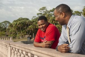 A young man leans on a railing with his male mentor | student mentoring program